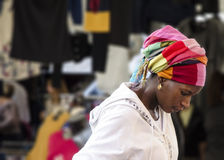 A colorful headdress. A beautiful young black girl with a colorful headdress looks down with a concentrated look stock image