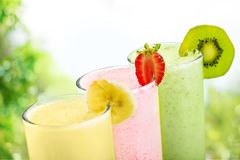 Colorful healthy milkshakes of different flovours. Green color red white background colorful isolated stock photo