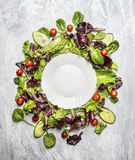 Colorful healthy salad with cucumber and tomatoes around white empty plate, on light gray wooden background, top view royalty free stock images