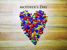 Happy Mother`s day colorful,heart. Colorful heart icon on a wooden background stock photos