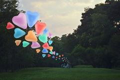 Colorful heart love balloon float on air with bicycle at park Royalty Free Stock Photo