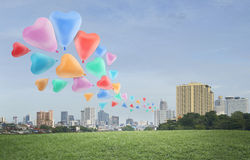Colorful heart love balloon float on air at city background Stock Image