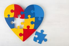 A colorful heart made of symbolic autism puzzle pieces. A colorful heart made of symbolic autism puzzle pieces on white wooden background Stock Image