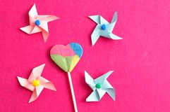 A colorful heart shape lollipop with colorful pinwheels on a pink background. A colorful heart shape lollipop displayed with colorful pinwheels on a pink Royalty Free Stock Photo