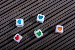 Heart shaped love cubes  on a straw mat. Colorful heart shaped love cubes  on a straw mat Royalty Free Stock Images