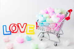 Colorful heart in shopping cart, love colorful foam heart. Stock Photos