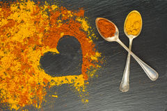Colorful heart from spices with two vintage spoons on black background with two vintage spoons. Selective focus. Valentines day. Royalty Free Stock Photos
