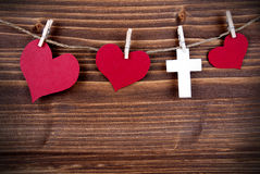 Colorful Hearts and a Cross Hanging on Wooden Background Stock Image
