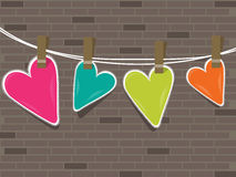 Colorful hearts hanging on a line against wall . Royalty Free Stock Images