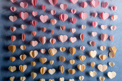 Colorful hearts paper garland hanging on the wall. Romantic Valentine's day background. Royalty Free Stock Photos