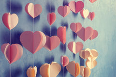 Colorful hearts paper garland hanging on the wall. Romantic Valentine's day background. Instagram style toned photo with copy spac Stock Images