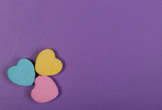 Colorful Hearts. Three Sweetheart Candy over purple background Royalty Free Stock Photo