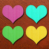 Colorful hearts on wood background Stock Photos