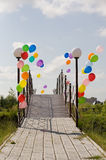 Colorful helium baloons at bridge opposite blue sky