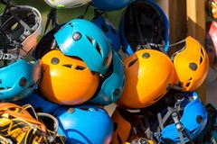 Colorful helmets for kids and adults in the rope park in summer at sunlights. Active sport royalty free stock images