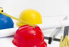 Colorful helmets and tools for construction drawings and buildin Royalty Free Stock Image