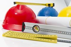 Colorful helmets and tools for construction drawings and buildin Royalty Free Stock Photos
