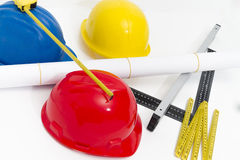 Colorful helmets and tools for construction drawings and buildin Royalty Free Stock Photo