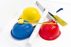 Colorful helmets and tools for construction drawings and buildin Royalty Free Stock Images