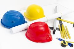 Colorful helmets and tools for construction drawings and buildin Royalty Free Stock Photography