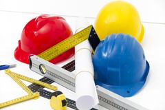 Colorful helmets and tools for construction drawings and buildin Stock Photos