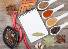 Colorful herbs and spices selection. Aromatic ingredients on wood table with blank notepad copyspace royalty free stock images