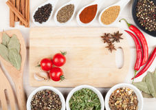 Colorful herbs and spices selection. Aromatic ingredients on wood table with cutting board for copyspace royalty free stock images