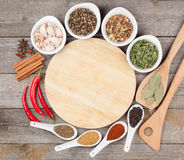 Colorful herbs and spices selection. Aromatic ingredients on wood table with empty cutting board for copyspace stock image