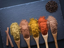 Colorful herbs and spices. In wooden spoons on black stone background,  top view Stock Photography