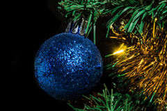 Colorful holiday background. Of a blue ball,Christmas tree and tinsel Royalty Free Stock Photography