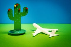 Holiday background with a small toy cactus and airplane. Colorful holiday background with a small toy cactus and a white airplane stock image