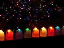 Colorful holiday lights. In strings across black background and inside plastic milk jugs Stock Photos