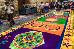 Colorful Holy Week carpet, Antigua, Guatemala. Antigua, Guatemala - April 2, 2015: Locals & purple robed float bearers (cucuruchos) walk past & admire dyed stock photography