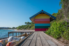 Colorful home and wooden walkway. Blue sky and mountain background Stock Photography