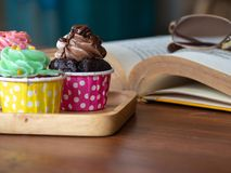 Colorful of homemade cupcake on wooden tray on and open book on wooden table. Concept of lifestyle and relax. Stock Photos