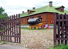 Colorful horse cart on the background of a wooden structure stock photography