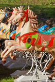 Colorful horses on a carousel Stock Photos