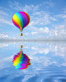 Colorful hot air ballon. 3d colorful Hot Air Balloon in the blue sky and reflection in water Stock Photos