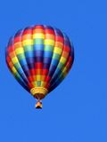 Colorful hot air balloon. Floating overhead in cloudless blue sky Royalty Free Stock Images