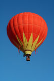 Colorful Hot Air Balloon. A very colorful hot air balloon soars in a clear blue sky Royalty Free Stock Photography