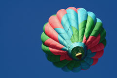 Colorful hot air balloon. Looking up at a colorful hot air balloon as it soars into a deep blue sky Royalty Free Stock Image