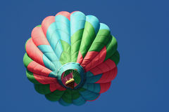 Colorful hot air balloon. Low angle view of colorful hot air balloon in flight with blue sky background Stock Image