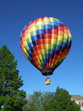 Colorful hot air balloon. Flying over green trees and house with blue sky background Stock Photos