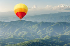 Colorful hot air balloon above forest mountain. Colorful hot air balloon above green forest mountain Royalty Free Stock Photography