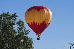 Red and Yellow Hot Air Balloon Descending Close to a Tree stock photo