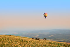 Colorful hot air balloon flying over an autumn landscape Royalty Free Stock Image