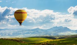 Colorful hot air balloon flying over green field stock image