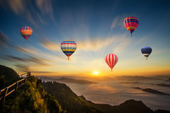 Colorful hot-air balloon flying over the mountain. At sunset Stock Image