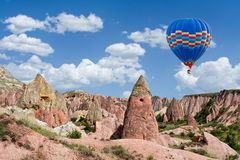 Colorful hot air balloon flying over Red valley at Cappadocia, Turkey Royalty Free Stock Photos