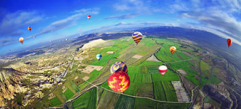 Colorful hot air balloon flying over rock landscape in  blue sky Stock Image